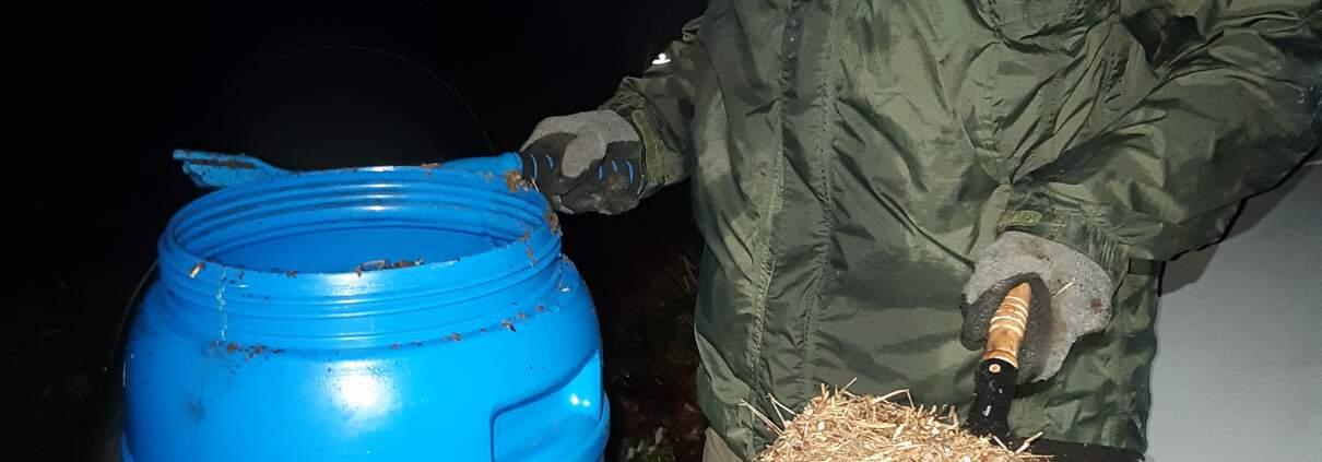 zdjęcie człowiek stoi koło beczki trzyma szufelkę w ręku przenoszenie mrowiska kompensacja