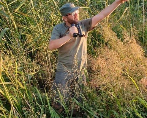 zdjęcie ornitolog trzyma lornetkę z uniesioną ręką skierowaną w niebo