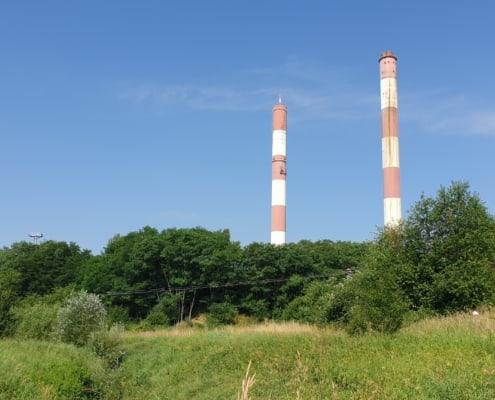zdjęcie łąki i lasu, dwa wysokie kominy na drugim planie na tle niebieskiego nieba